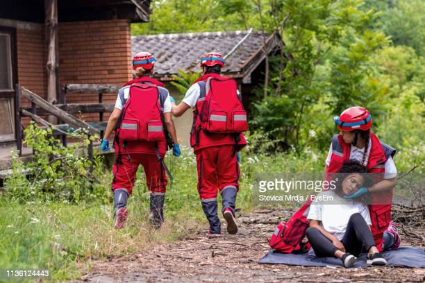 rescue worker with injured woman against colleagues walking towards house during tornado - rescue worker stock pictures, royalty-free photos & images