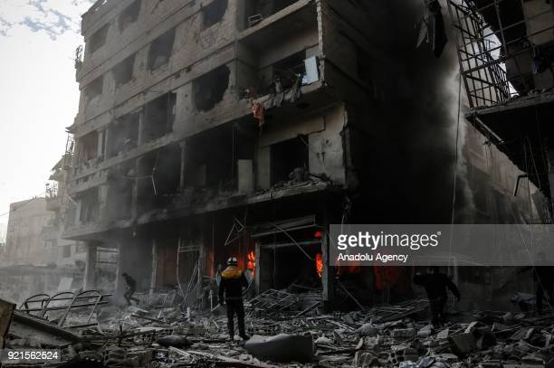 Rescue workers and citizens intervene the fire in wreckage of a building after Assad Regime carried out an airstrike over Sakba town of Eastern...