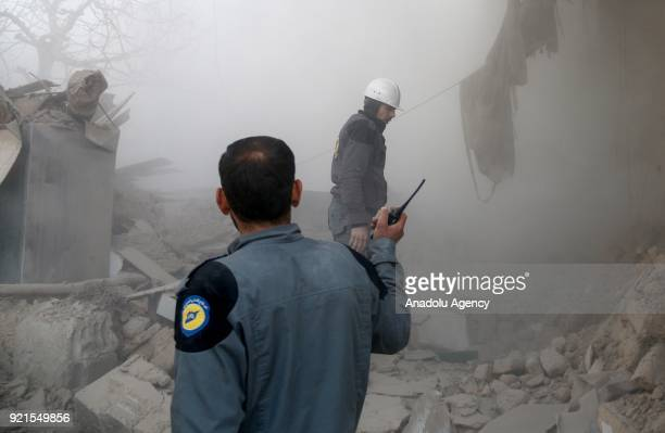 Rescue workers and citizens search and inspect the debris of buildings after Assad Regime carried out an airstrike over Arbin town of the Eastern...