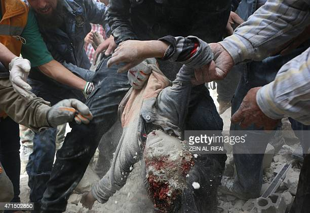 Rescue workers and civilians carry the body of a child after pulling it from the rubble of a building that was targeted in a reported barrel bomb...