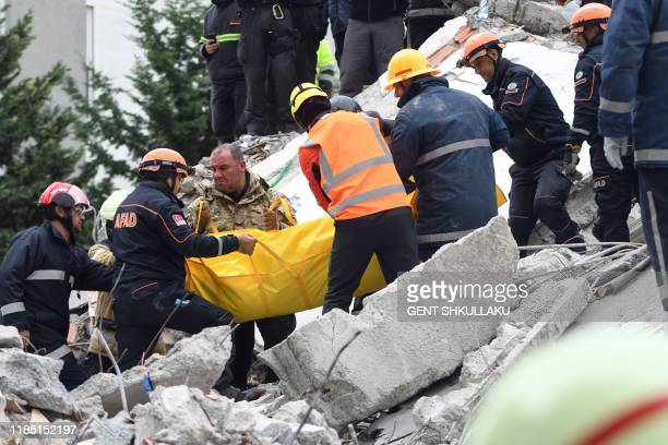 Rescue workers and firefighters carry the body of a victim found under the rubble of a collapsed building in the town of Durres western Albania on...