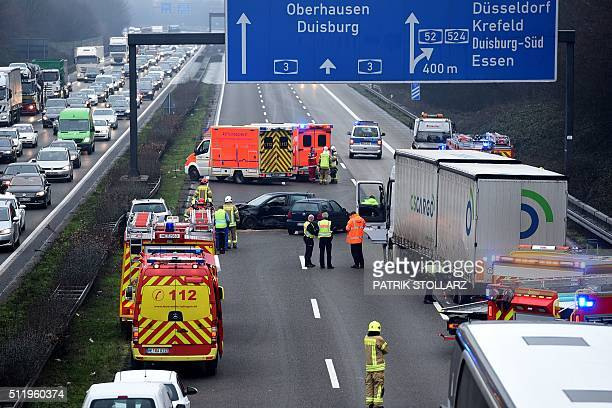 Rescue workers and firefighters clean up the A3 motorway near Essen after a car crash caused a traffic jam on Feruary 24 2016 in Essen western...