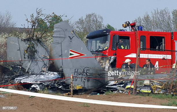 Rescue workers and firefighters gather around the wreckage of a Hungarian air force MiG29 fighter aircraft that ploughed into the ground on April 17...