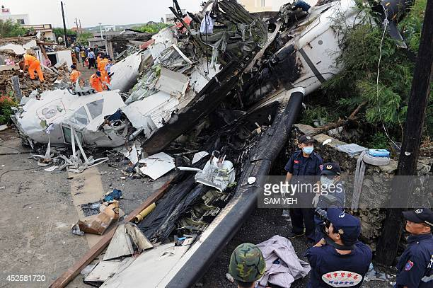 Rescue workers and firefighters search through the wreckage where TransAsia Airways flight GE222 crashed the night before near the airport at Magong...