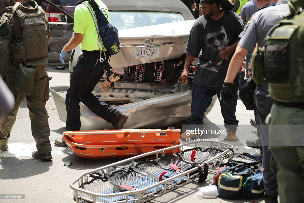 Rescue workers and medics tend to people who were injured as a car with the license plate GODKPME that was hit after another car plowed through a crowd of counter-demonstrators marching through the downtown shopping district August 12, 2017 in Charlottesville, Virginia. The car plowed through the crowed following the shutdown of the 'Unite the Right' rally by police after white nationalists, neo-Nazis and members of the 'alt-right' and counter-protesters clashed near Emancipation Park, where a statue of Confederate General Robert E. Lee is slated to be removed.