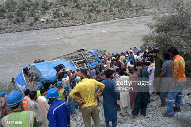 Rescue workers and onlookers gather around a wreck after a bus plunged into a ravine following a bomb explosion, which killed 12 people including 9...