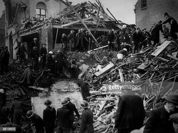 Rescue workers and police clamber over the wreckage of a junior school in Liverpool bombed during a German air raid