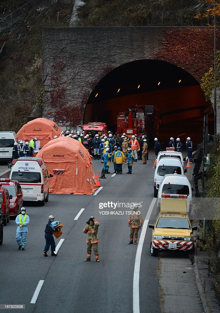 Rescue workers and police gather outside the Sasago tunnel along the Chuo highway near the city of Otsuki in Yamanashi prefecture, 80 kms west of Tokyo on December 2, 2012 after part of the tunnel collapsed. Japanese rescuers found several charred bodies in the highway tunnel that collapsed early in the day, crushing cars and triggering a blaze, and sparking fears of another cave-in. AFP PHOTO / Yoshikazu TSUNO