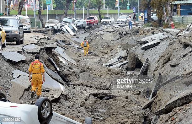 Rescue workers and their dog search through the site after gas explosions in the southern city of Kaohsiung on August 1 2014 A series of powerful gas...