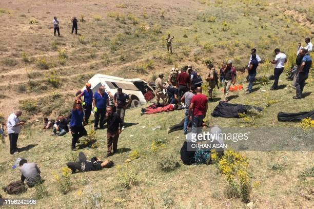 Rescue workers and Turkish soldiers take care of injured migrants after a minibus accident in Van, eastern Turkey, on July 18, 2019. - Fifteen people...