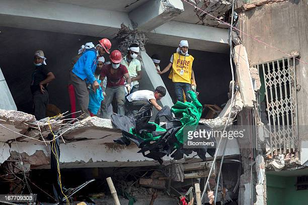 Rescue workers and volunteers remove clothing garments from the building as they search for victims amongst the collapsed Rana Plaza building in...