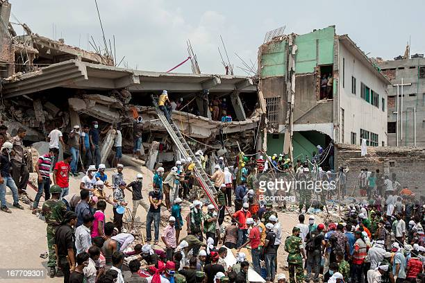Rescue workers and volunteers search by hand for victims amongst the debris of the collapsed Rana Plaza building in Dhaka, Bangladesh, on Friday,...