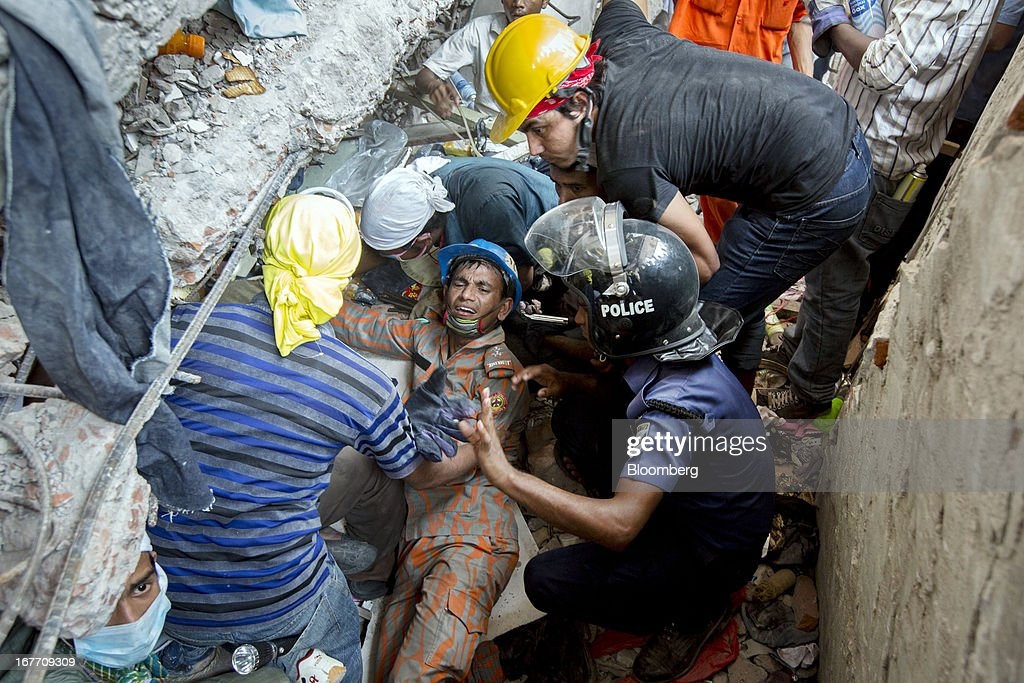 Rescue workers and volunteers search by hand for victims amongst the debris of the collapsed Rana Plaza building in Dhaka, Bangladesh, on Friday, April 26, 2013. The day after a Bangladesh building collapsed, killing more than 290 people, disagreement emerged over whether the owner obtained appropriate construction permits, adding to concerns over worker safety in the country's garment industry. Photographer: Jeff Holt/Bloomberg via Getty Images