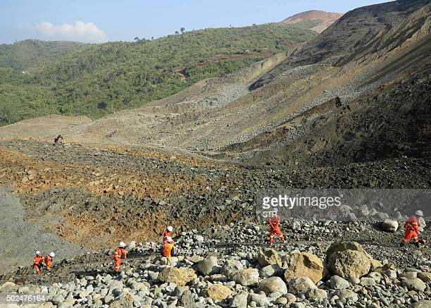 Rescue workers are pictured at the site of a landslide on December 26 2015 in Hpakant Kachin State the wartorn area that is the epicentre of...