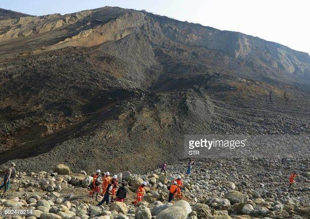TOPSHOT Rescue workers are pictured at the site of a landslide on December 26 2015 in Hpakant Kachin State the wartorn area that is the epicentre of...