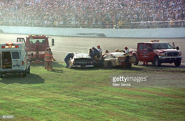 Rescue workers arrive at Dale Earnhardt's Goodwrench Chevrolet after a crash during the running of the 43rd Daytona 500 at the Daytona International...