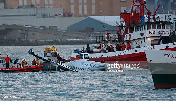 Rescue workers assist a New York City Fire Department boat pulled near a US Airways plane floating in the water after crashing into the Hudson River...