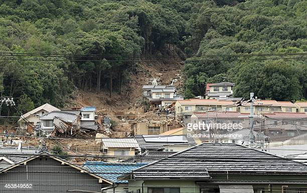 Rescue workers at the site of a landslide in a residential area on August 20, 2014 in Hiroshima, Japan. At least 18 people were confirmed dead and...