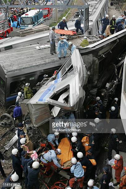 Rescue workers attempt to free trapped passengers from a crushed commuter train after it derailed and plunged into an apartment building on April 25...