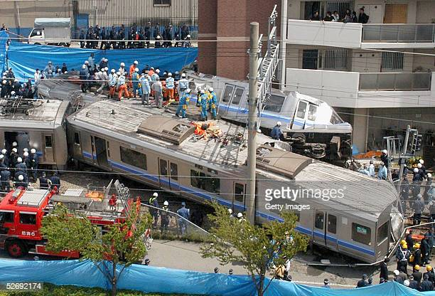 Rescue workers attempt to free trapped passengers from a crushed commuter train after it derailed and plowed into an apartment building on April 25...