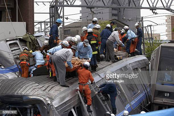 Rescue workers attempt to free trapped passengers from a crushed commuter train after it derailed and ploughed into an apartment building on April 25...