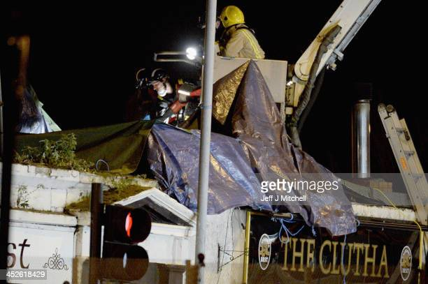 Rescue workers attend the scene at a pub on Stockwell Street where a police helicopter crashed on the banks of the River Clyde November 30 2013 in...