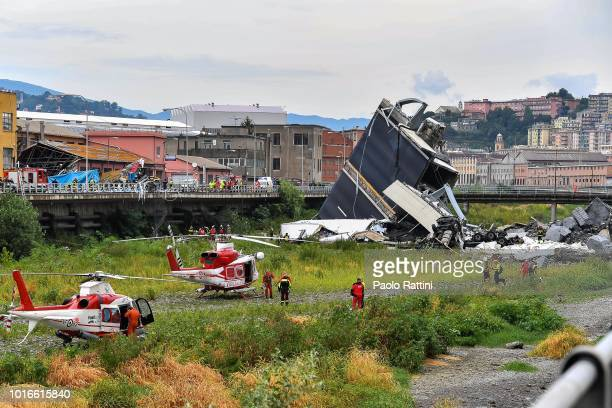 Rescue workers attend the scene at the Morandi bridge which collapsed on August 14 2018 in Genoa Italy At at least 22 people have died when a large...