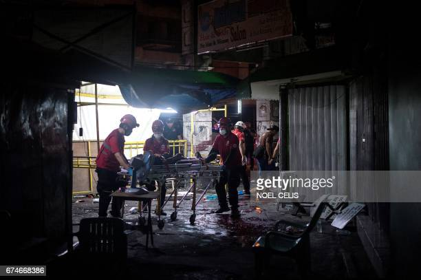TOPSHOT Rescue workers attend to a wounded man on a stretcher in an alley in Manila on April 28 after a homemade pipe bomb exploded Fourteen people...