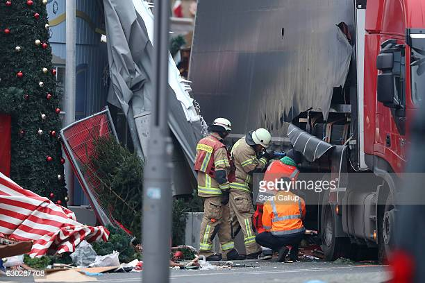 Rescue workers begin to remove the rear of the lorry the morning after it ploughed through a Christmas market on December 20 2016 in Berlin Germany...