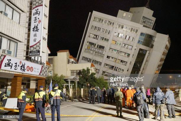 TOPSHOT Rescue workers block off the area to search for survivors outside a building which tilted to one side after its foundation collapsed in...
