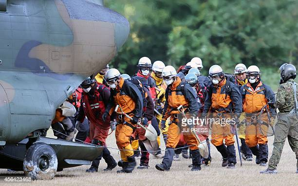 Rescue workers board on a defense forces helicopter heading for the top of Mount Ontake for a search and rescue operation following the September 27...