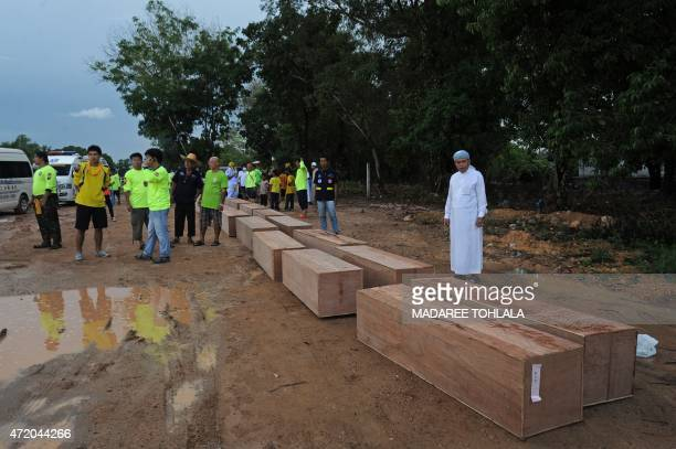 Rescue workers bring coffins containing the human remains of migrants exhumed the day before from a mass grave at an abandoned jungle camp in the...