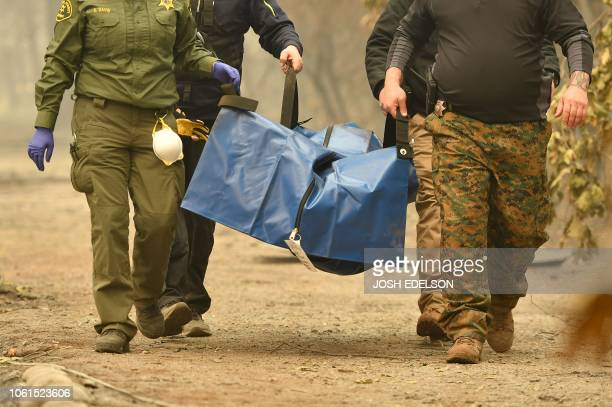 TOPSHOT Rescue workers carry a body away from a burned property in the Holly Hills area of Paradise California on November 14 2018 Firefighters...
