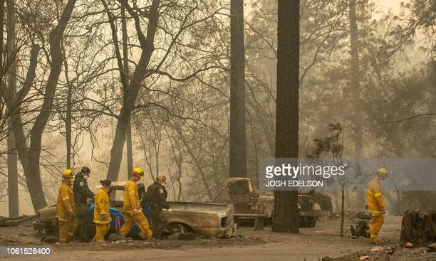 Rescue workers carry a body away from a burned property in the Holly Hills area of Paradise California on November 14 2018 Firefighters backed by air...