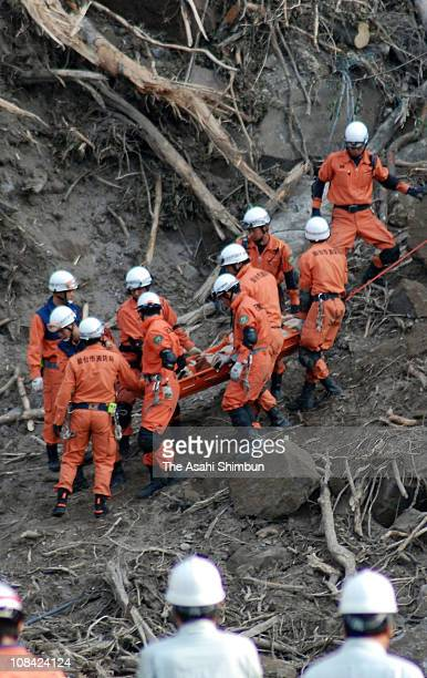 Rescue workers carry a body of the victim who was involved to a landslide caused by a strong earthquake on June 20 2008 in Kurihara Miyagi Japan