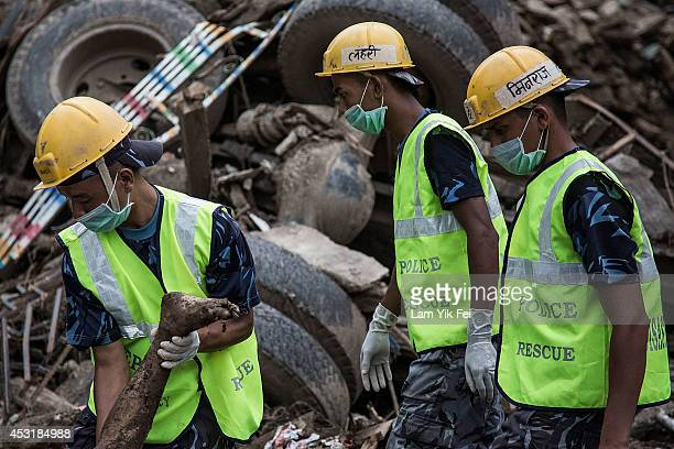 Rescue workers carry a dead body at the scene of a landslide in the district of Sindhupalchowk which is 120 km east of Kathmandu, on August 4, 2014....