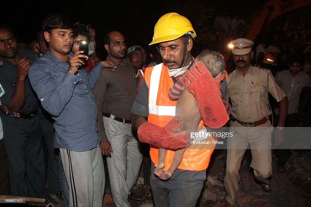 Rescue workers carry a infant child who survived the building collapse at Lucky compound on April 4, 2013 in Thane, India. The death toll has risen to 39 while at least 69 people are injured. The building is illegal and constructed on Forest land. Police have registered a case against builders Salil and Khalil Jamadar under Section 304.