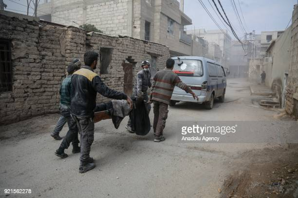 Rescue workers carry a wounded man on a stretcher who was saved alive inside the debris of buildings after Assad Regime carried out an airstrike over...