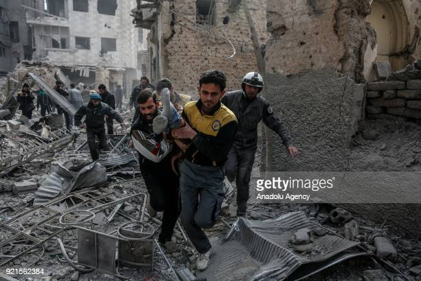 Rescue workers carry a wounded man who was saved alive inside the debris of buildings after Assad Regime carried out an airstrike over Sakba town of...