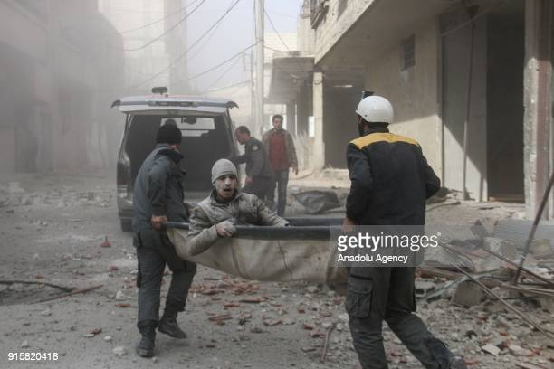 Rescue workers carry a wounded man with a stretcher as they conduct search and rescue operations on debris of destroyed buildings after Assad Regime...
