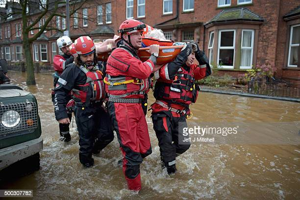 Rescue workers carry an elderly woman as teams continue to evacuate people from their homes after Storm Desmond caused flooding on December 7 2015 in...