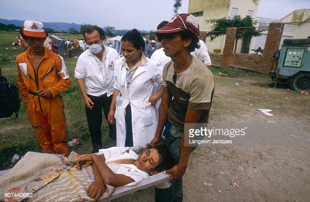 Rescue workers carry an injured person, caught in a lahar flowing from the erupting Nevado del Ruiz volcano in Colombia, on a stretcher. The 1985...