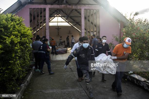 Rescue workers carry bodies of victims of mudslides at the cemetery in Villagarzon Putumayo department southern Colombia on April 1 2017 Massive...