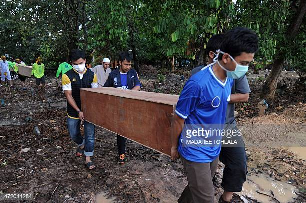 Rescue workers carry coffins containing the human remains of migrants exhumed the day before from a mass grave at an abandoned jungle camp in the...