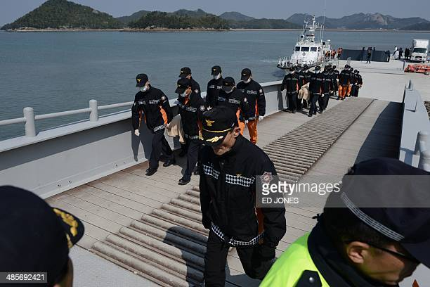 Rescue workers carry the bodies of a victim from the sinking of the South Korean ferry 'Sewol' upon arrival at Jindo harbour on April 20 2014 Divers...