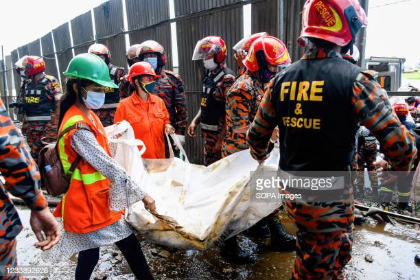 Rescue workers carry the bodies that were discovered after a fire broke out at a factory of Hashem Foods Ltd in Rupganj, Narayanganj district, on the...