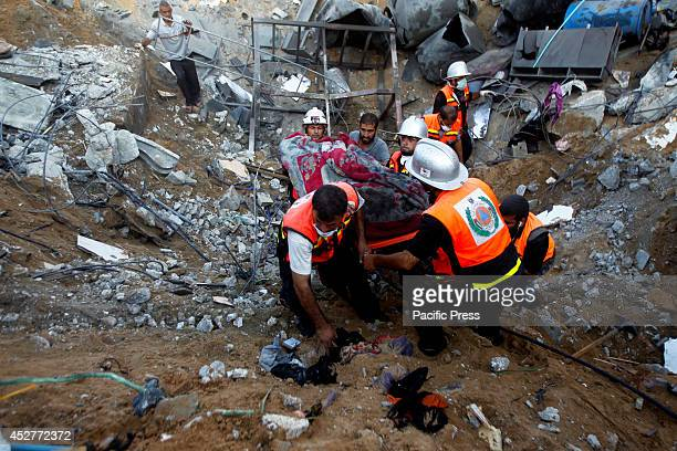 Rescue workers carry the body of a member of al-Najar family, after removing it from under the rubble of their home following an Israeli air strike...