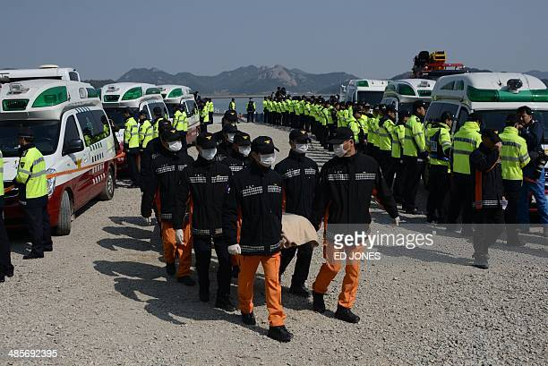 Rescue workers carry the body of a victim from the sinking of the South Korean ferry 'Sewol' upon arrival at Jindo harbour on April 20 2014 Divers...