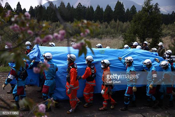 Rescue workers carry the body of a woman under tarpaulin after she was found in a house that was destroyed by a mudslide following an earthquake, on...