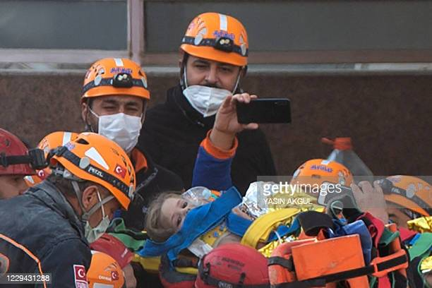Rescue workers carry three-year-old girl Ayda Gezgin as they pull her out of the rubble of a building 91 hours after it collapsed during a...